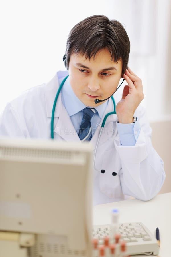 Medische arts in hoofdtelefoon die in bureau werkt stock foto