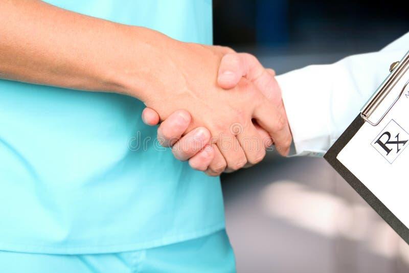 Medische arts met een stethoscoop rond zijn hals het schudden hand met collega royalty-vrije stock afbeelding