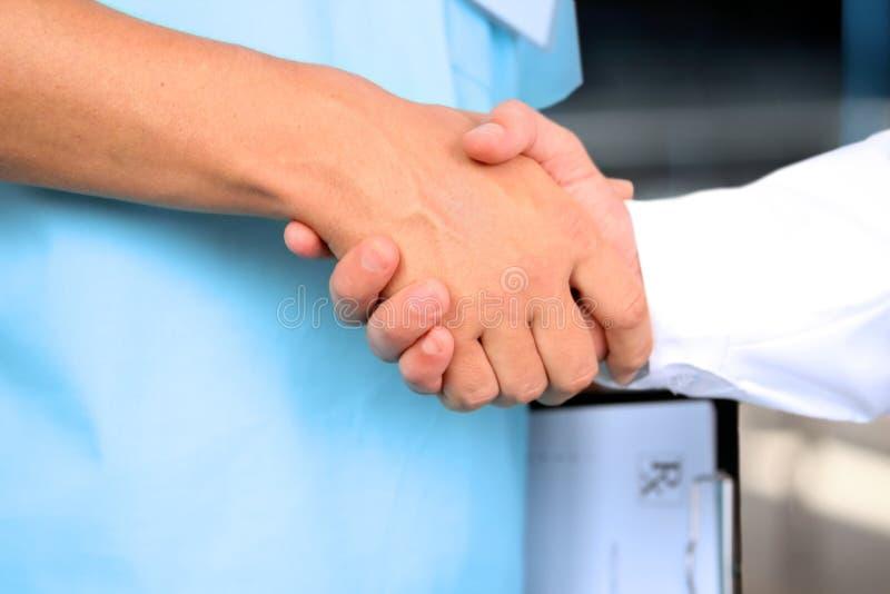 Medische arts met een stethoscoop rond zijn hals het schudden hand met collega stock foto's