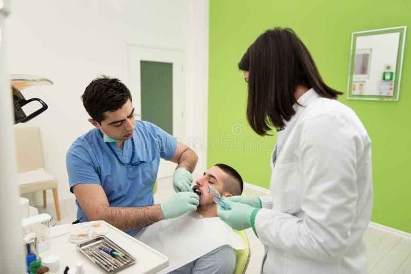 Medische behandeling een patiënt met een tandpijn royalty-vrije stock foto's