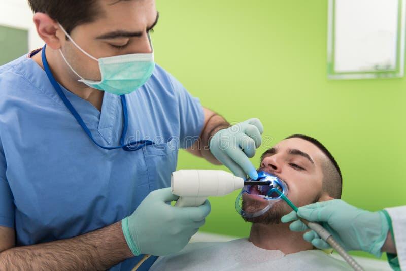 Medische behandeling een patiënt met een tandpijn stock afbeelding