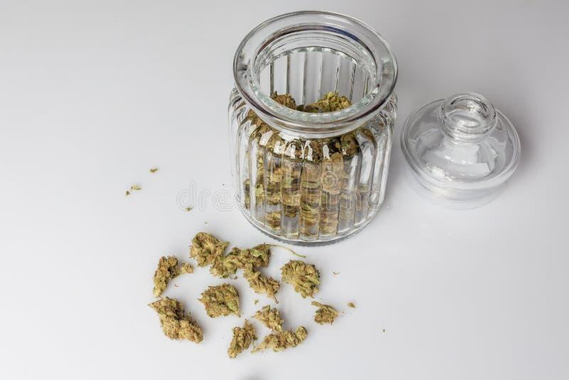 Medische cannabis in glaskruik op wit vanuit hoge invalshoek stock foto's
