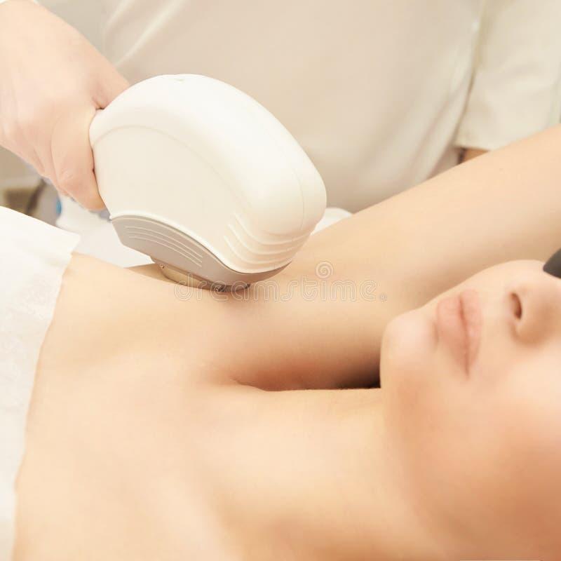 Medische cosmeologyprocedure van de schoonheidslaser Jong wijfje bij salon Professionele arts Vrouwen skincare technologie Haarve stock fotografie