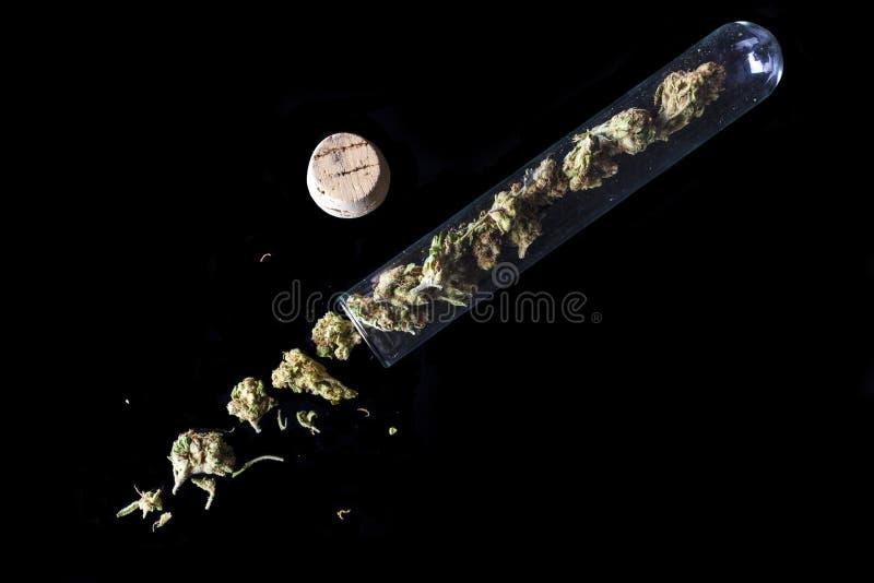 Medische die cannabis van reageerbuis op zwarte hoge hoek wordt gemorst royalty-vrije stock foto