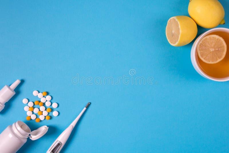 Medische elektronische thermometer, medicijnfles met pillen, nevel voor neus en thee met citroen op blauwe achtergrond Mede gezon royalty-vrije stock afbeelding