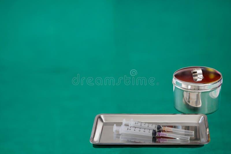 Medische het dienbladspuit van de hulpmiddelenkruik op groene achtergrond met exemplaar tex royalty-vrije stock afbeelding