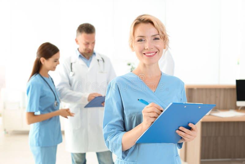 Medische medewerker met collega's in kliniek stock foto