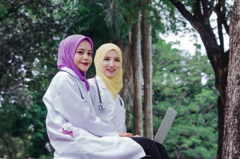 Medische muslimah artsen die een rust en een bespreking hebben bij park stock afbeelding