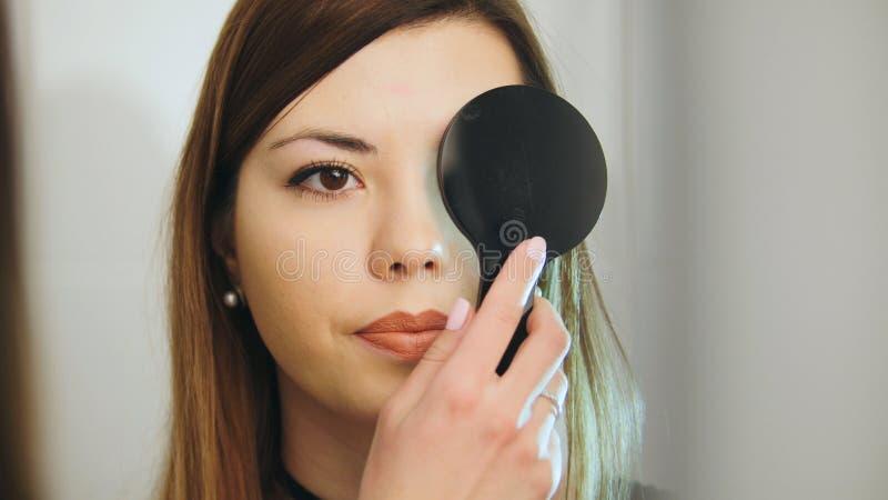 Medische oftalmologie, gezondheid, concept - het mooie meisje controleert visie in een oftalmoloog met één gesloten oog royalty-vrije stock foto