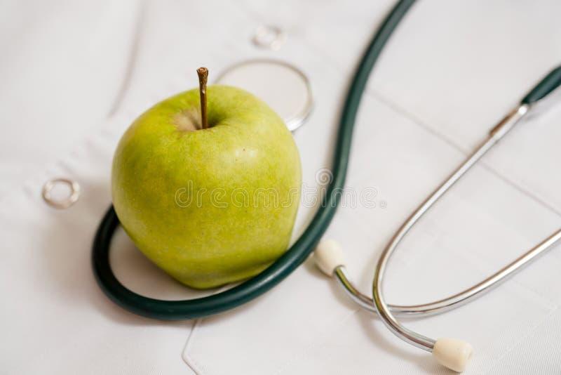 Medische phonendoscope op een medische peignoir Een groene appel is een madeliefjebloem Concept gezondheid stock foto