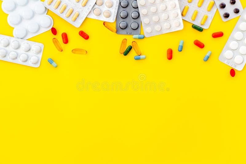 Medische pillen, antibiotica die voor zorg en gezondheid op gele achtergrond hoogste meningsruimte nemen voor tekst royalty-vrije stock afbeelding