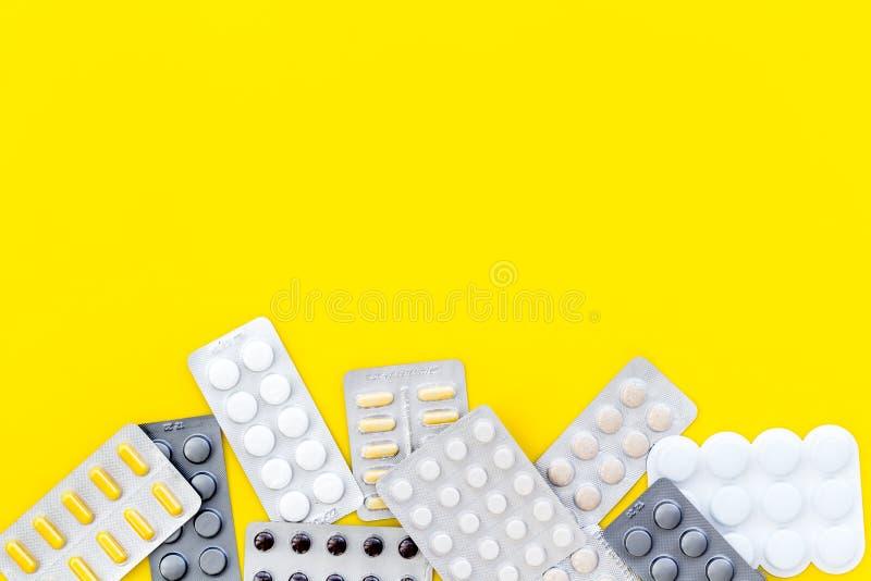 Medische pillen, antibiotica die voor zorg en gezondheid op gele achtergrond hoogste meningsruimte nemen voor tekst stock afbeelding