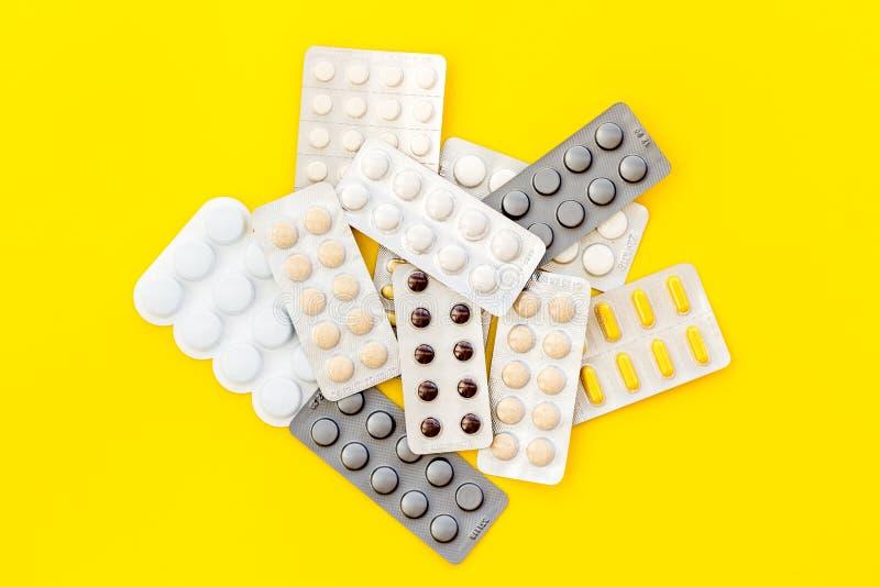 Medische pillen, antibiotica die voor zorg en gezondheid op gele hoogste mening nemen als achtergrond royalty-vrije stock fotografie