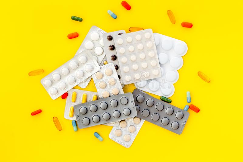 Medische pillen, antibiotica die voor zorg en gezondheid op gele hoogste mening nemen als achtergrond royalty-vrije stock foto