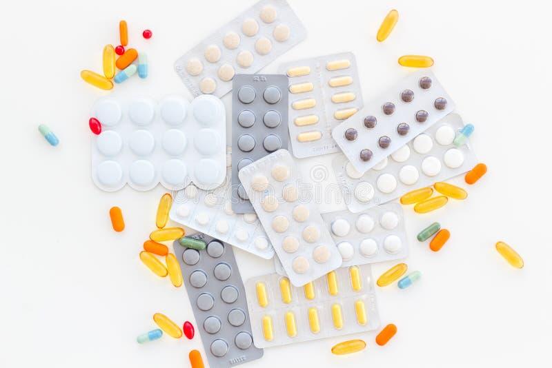 Medische pillen, antibiotica die voor zorg en gezondheid op witte hoogste mening nemen als achtergrond stock foto