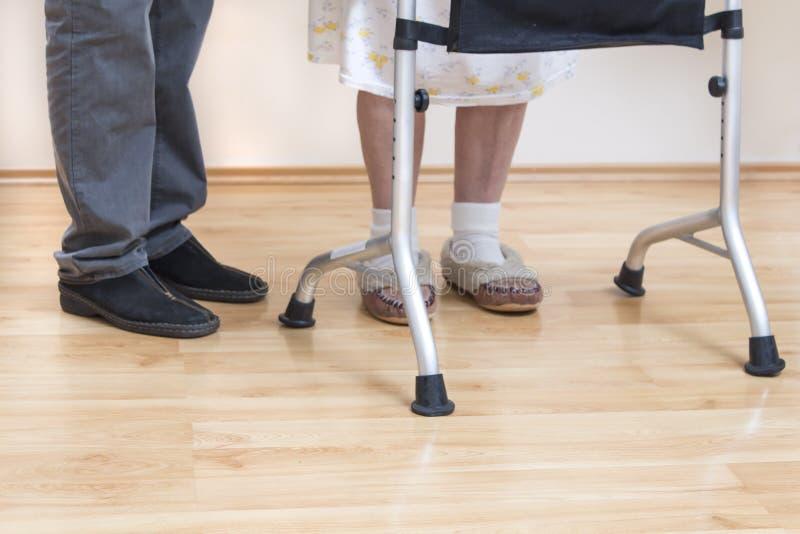 Medische rehabilitatiebalkons De oma leert om met behulp van een leurder en bijgewoond door een verpleegster te lopen stock foto's