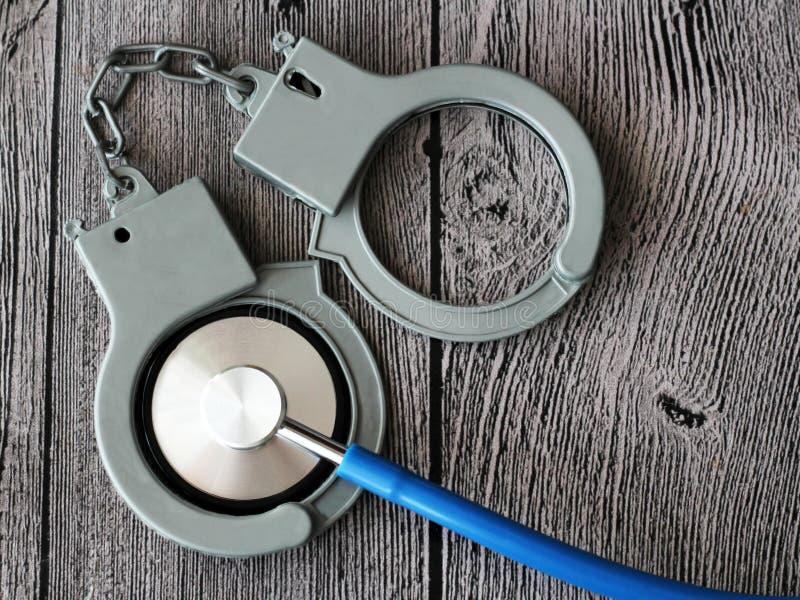 Medische stethoscoop en handcuffs op houten achtergrond stock foto's