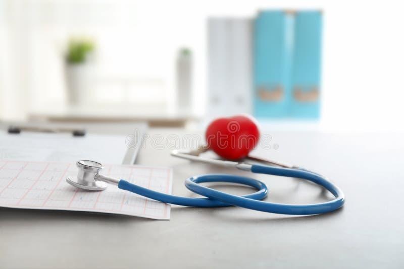 Medische stethoscoop en rood hart op grijze lijst Het concept van de cardiologie stock fotografie