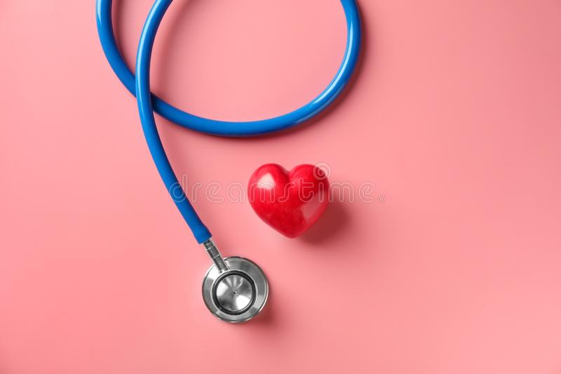 Medische stethoscoop en rood hart op kleurenachtergrond Het concept van de cardiologie royalty-vrije stock foto's