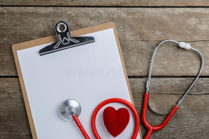 Medische stethoscoop met klembord en hart op houten lijst stock fotografie