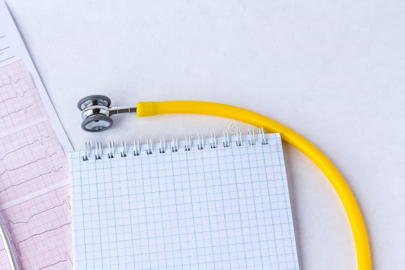 Medische stethoscoop op cardiogramgrafiek met een notitieboekje hoogste mening met ruimte voor tekst stock foto's