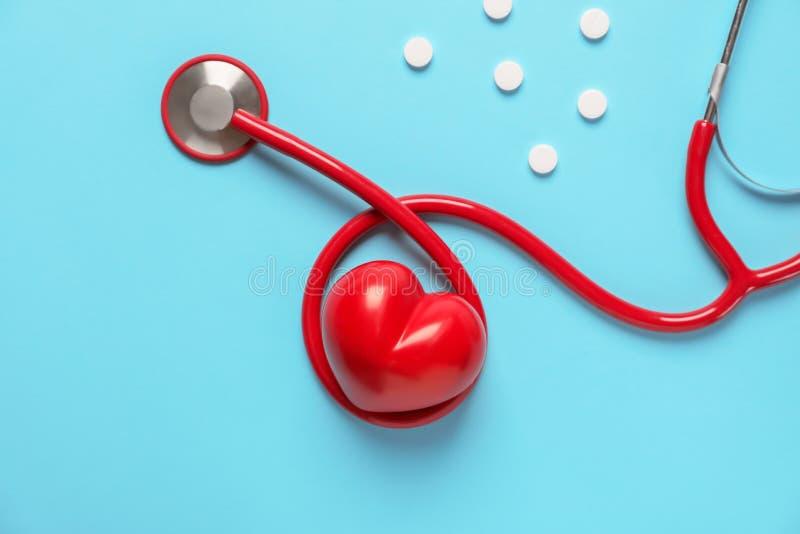 Medische stethoscoop, pillen en rood hart op kleurenachtergrond Het concept van de cardiologie stock afbeelding