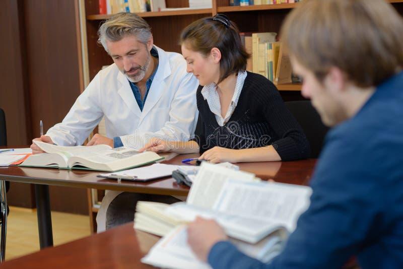 Medische studenten die in bibliotheek met arts bestuderen stock foto