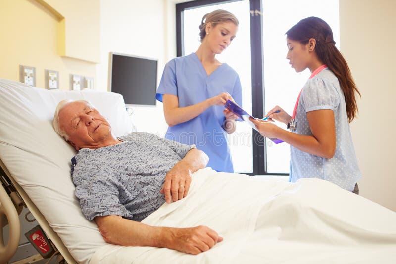 Medische Team Meeting As Senior Man-Slaap in het Ziekenhuiszaal royalty-vrije stock foto's