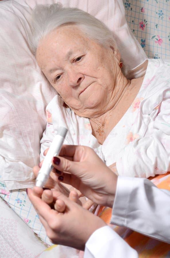 Medische verpleegster die het niveau van de bloedsuiker meten stock afbeeldingen