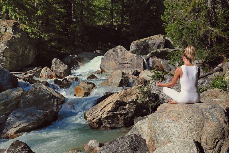 Meditação da mulher por um córrego foto de stock royalty free