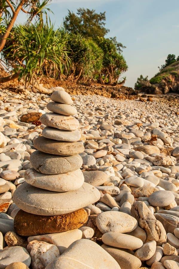 A meditação do zen do monte de pedras, pedras equilibra na praia de pedra, árvores tropicais e a montanha borrou fundos Ilha de L imagens de stock royalty free