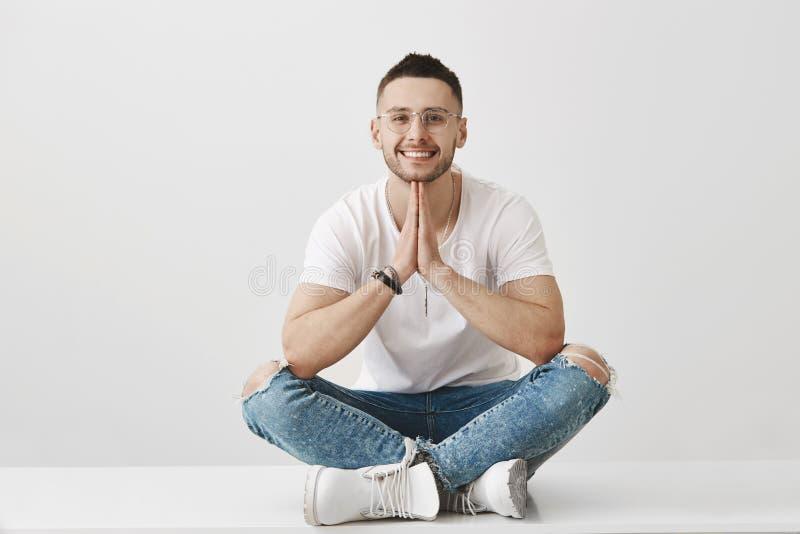 Meditação e conceito das emoções Homem novo à moda atrativo com a barba, os vidros vestindo e o equipamento na moda, sentando-se foto de stock royalty free