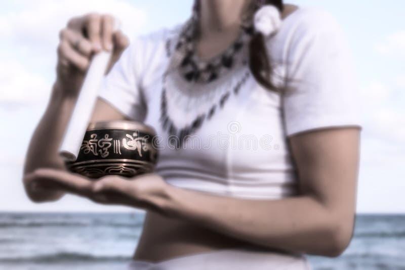 MEDITAÇÃO NA PRAIA com sino tibetano fotografia de stock royalty free