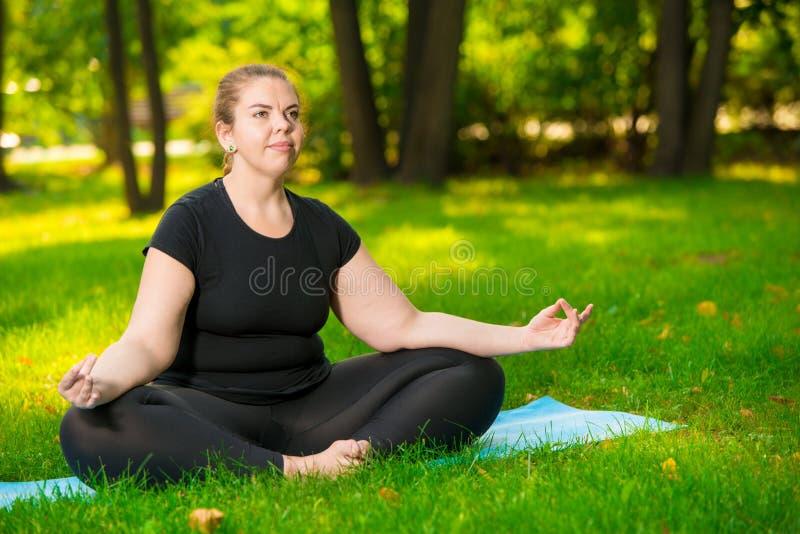 meditação no parque, um retrato de um modelo focalizado sobre o tamanho durante uma ioga fotos de stock