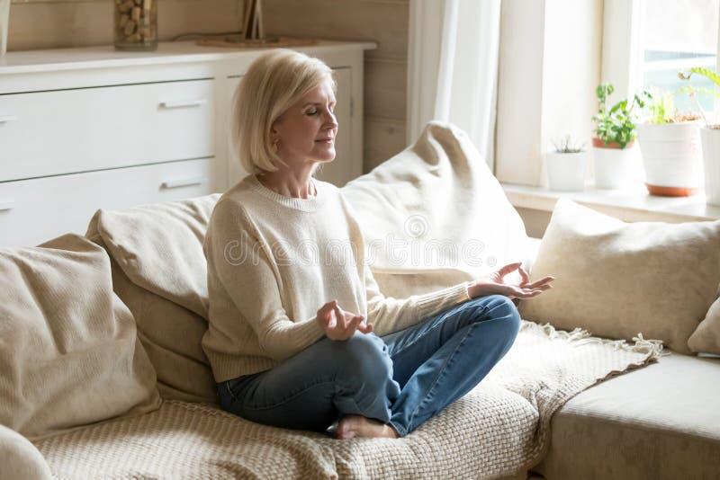 Meditação praticando da ioga da mulher madura saudável consciente em casa fotos de stock