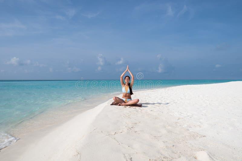 Medita??o - mulher da ioga que medita na praia sereno imagem de stock
