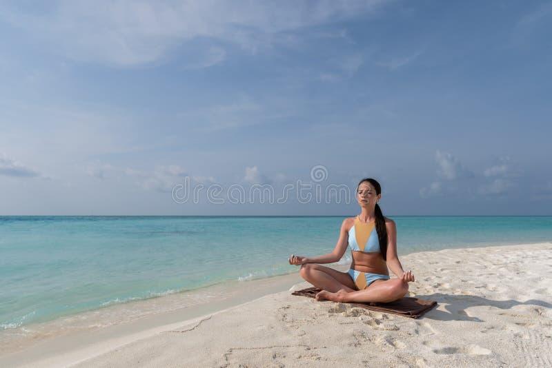 Medita??o - mulher da ioga que medita na praia sereno fotos de stock