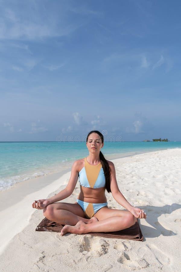 Medita??o - mulher da ioga que medita na praia sereno fotos de stock royalty free
