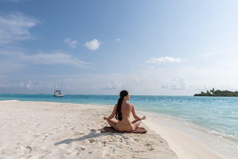 Medita??o - mulher da ioga que medita na praia sereno imagem de stock royalty free