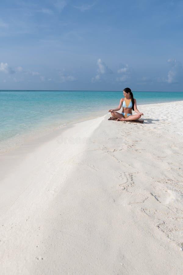 Medita??o - mulher da ioga que medita na praia sereno foto de stock