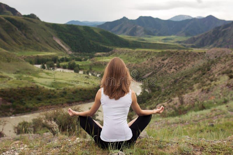 Meditación al aire libre de la mujer joven El sentarse en la montaña imagen de archivo