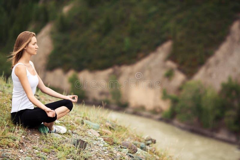 Meditación al aire libre de la mujer joven El sentarse en la montaña foto de archivo