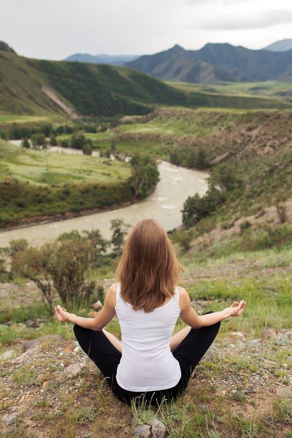 Meditación al aire libre de la mujer joven El sentarse en la montaña imágenes de archivo libres de regalías