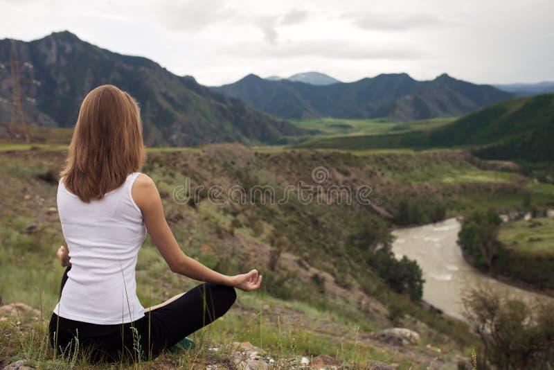 Meditación al aire libre de la mujer joven El sentarse en la montaña fotografía de archivo libre de regalías
