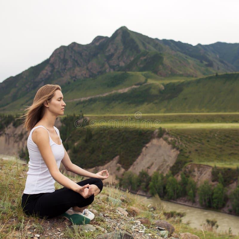 Meditación al aire libre de la mujer joven El sentarse en la montaña fotos de archivo libres de regalías