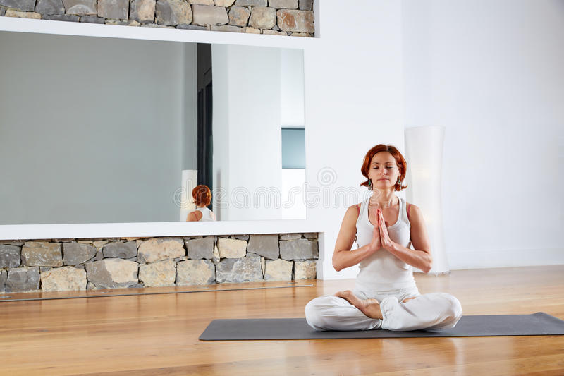 Meditación de la actitud de Lotus de la yoga en piso de madera imagen de archivo libre de regalías