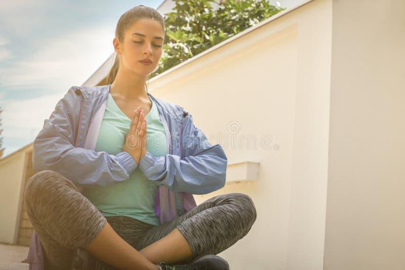 Meditación de la chica joven en la acera imagen de archivo libre de regalías