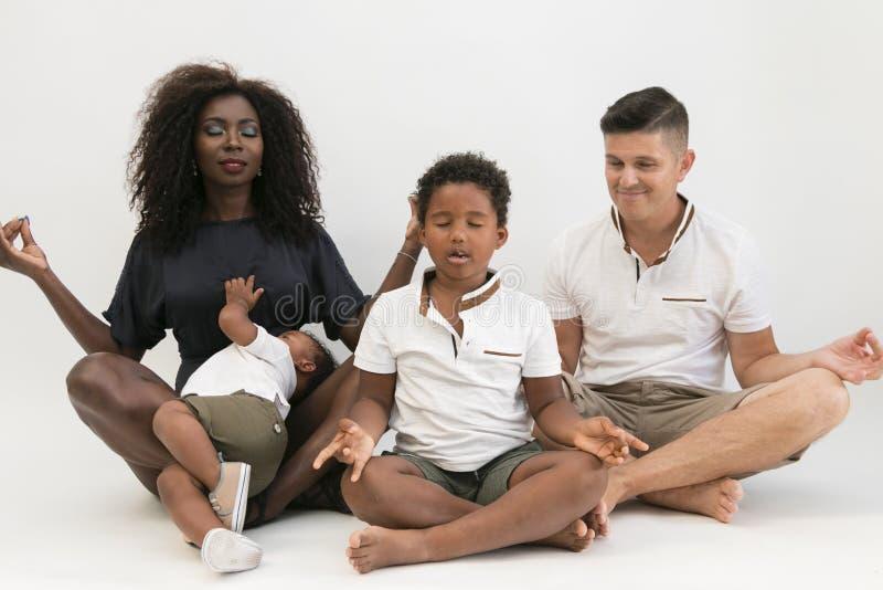 Meditación de la familia de la raza mixta que se relaja con yoga Vida equilibrada c imagen de archivo
