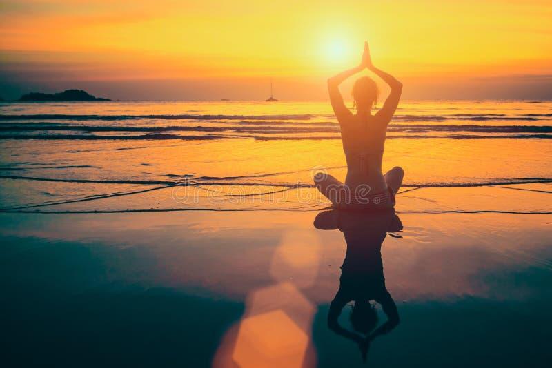 Meditación de la mujer de la yoga en costa de mar de la puesta del sol foto de archivo libre de regalías