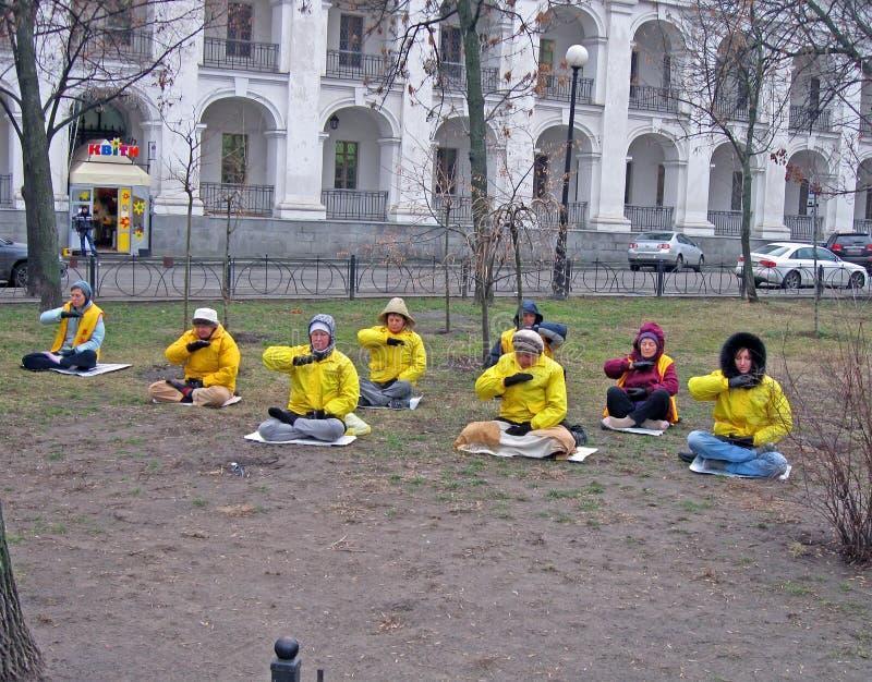 Meditación de la yoga, gente en chaquetas amarillas, fotos de archivo libres de regalías